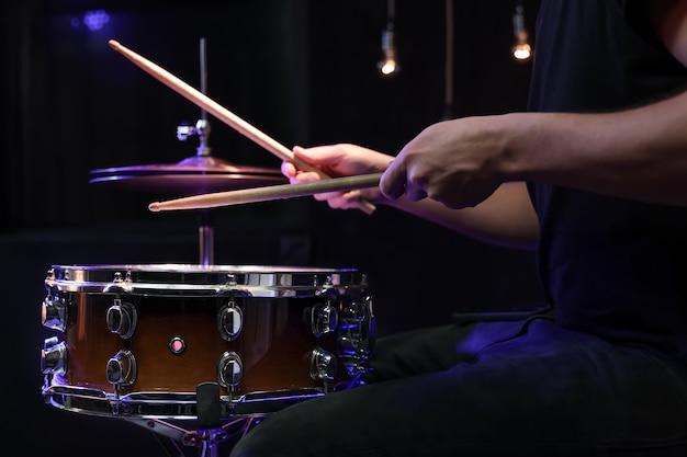 Batteur jouant des baguettes sur une caisse claire dans l'obscurité. concept de concert et de performance en direct.