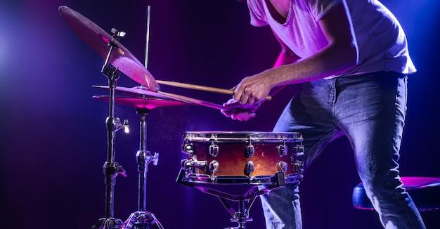 Un batteur joue de la batterie sur un mur bleu