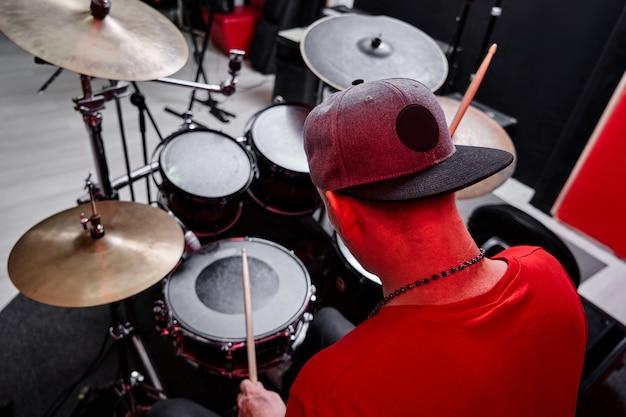 Le batteur professionnel moderne joue de la batterie sur une base de répétition, studio d'enregistrement rouge et noir
