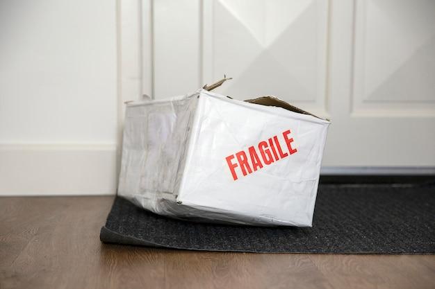 Battre la boîte de livraison endommagée avec un autocollant fragile, emballage en carton livré cassé à la maison