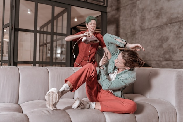 Battre l'homme. femme en colère aux cheveux verts battant son homme avec du fer après un combat agressif