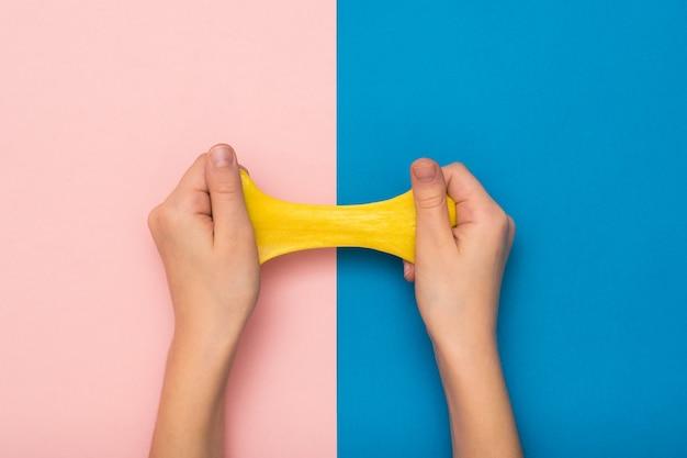 Bave jaune étirée par les mains des enfants sur fond rose et bleu. jouet antistress. jouet pour le développement de la motricité de la main.