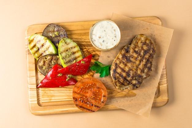 Bbq steak, viande, légumes courge aubergines et tomates, poivrons rôtis sur une planche de bois. vue de dessus sur une surface brune.
