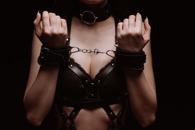 Bdsm. fille menottes aux poignets et sous-vêtements sexy en cuir noir bouchent
