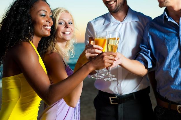 Beach party avec des amis portant un toast au champagne