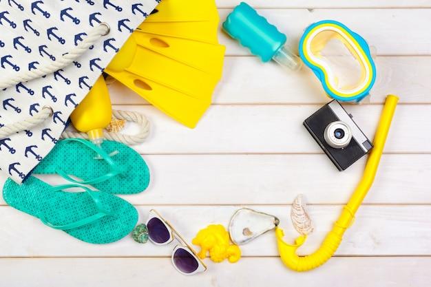Beachwear et accessoires sur un fond en bois blanc