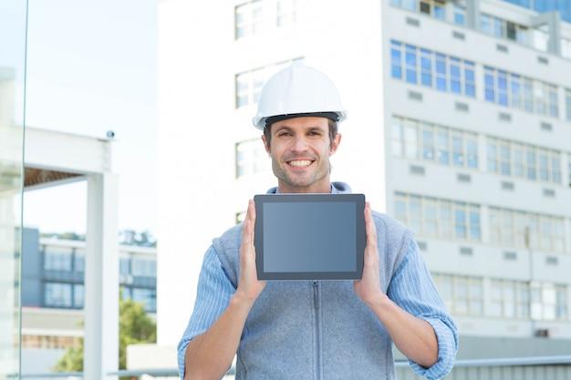 Beau architecte mâle montrant une tablette numérique