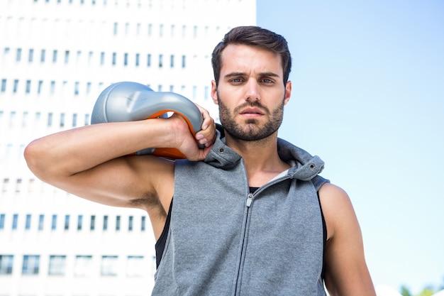 Beau athlète tenant une cloche de bouilloire