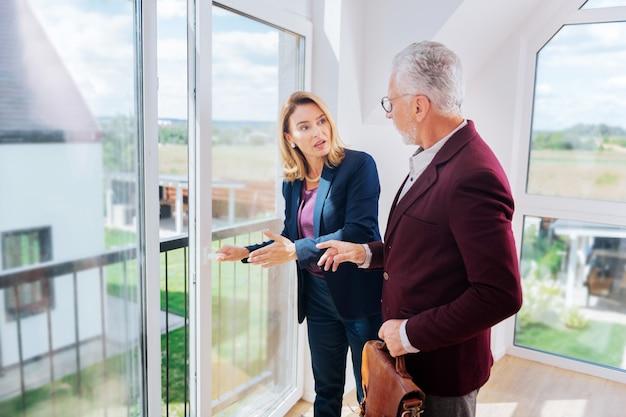 Beau balcon. agent immobilier aux cheveux blonds montrant joli balcon de maison moderne son riche client d'affaires prospère