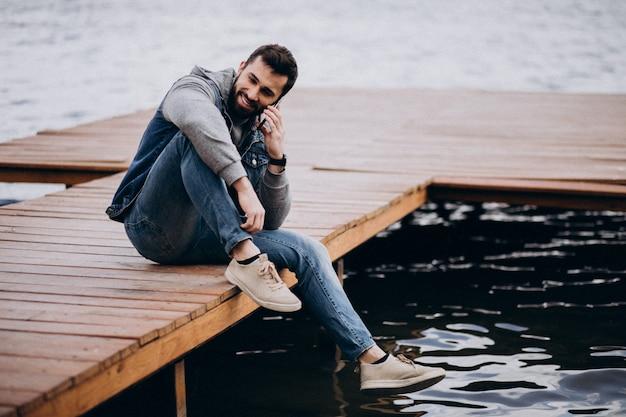 Beau barbu à la rivière dans le parc assis sur le quai