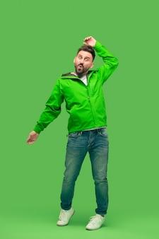 Beau barbu souriant heureux jeune homme regardant la caméra isolée sur studio vert branché vif. concept de l'automne et du temps froid
