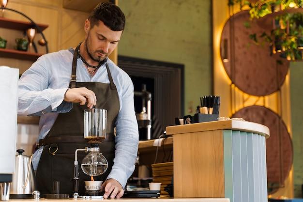 Beau barista barbu mélanger du café fraîchement moulu dans un dispositif de siphon pour la préparation du café au café