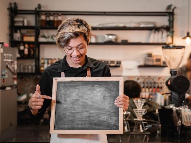 Beau barista tenant et pointant un tableau noir sur le stand devant pub