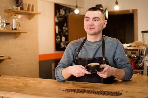 Beau barista tenant une tasse de café au café