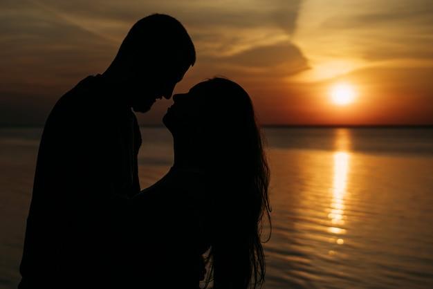Un beau beau couple amoureux à l'aube se regarde en gros plan et sourit.