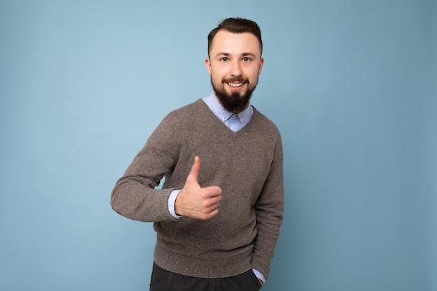 Beau beau jeune homme barbu brun portant un pull gris et une chemise bleue isolé sur fond rose avec un espace vide regardant la caméra et montrant le geste du pouce levé
