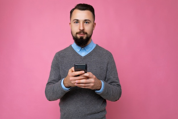 Beau beau jeune homme barbu brunet portant un pull gris et une chemise bleue isolée sur rose