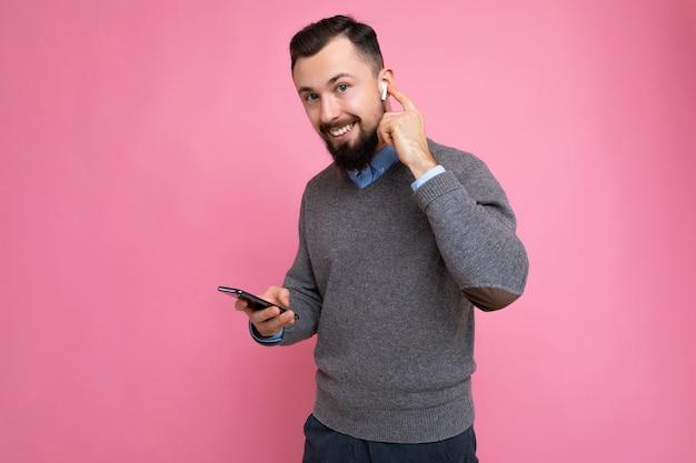 Beau beau jeune homme barbu brunet vêtu d'un pull gris et d'une chemise bleue isolé sur fond rose avec un espace vide tenant dans la main et utilisant un téléphone portable communiquant en ligne en regardant c