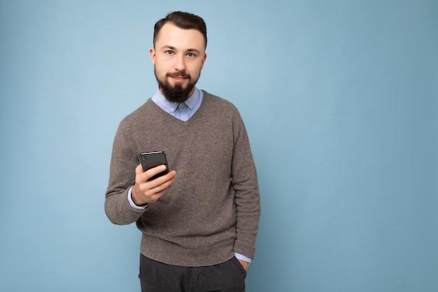 Beau beau jeune homme barbu portant un pull gris et une chemise bleue isolé sur rose