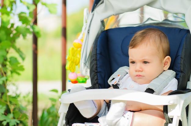 Beau bébé assis dans un landau à l'extérieur