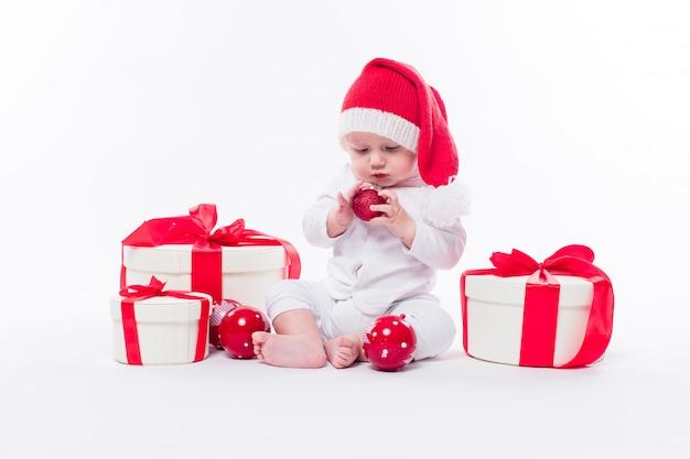 Beau bébé dans le bonnet du nouvel an et le corps blanc est assis