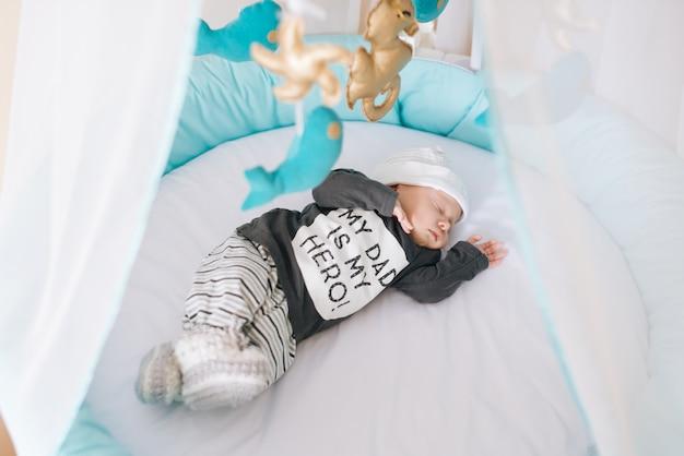 Beau bébé nouveau-né allongé dans un lit ovale avec de beaux pare-chocs dans des tons délicats de gris, bleu et blanc
