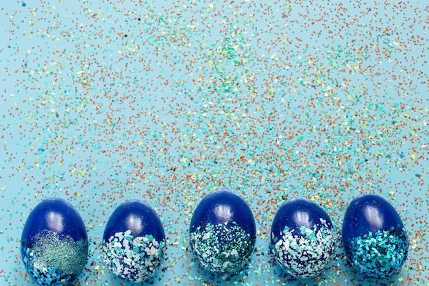 Beau bleu de pâques avec des oeufs décoratifs bleus en paillettes.
