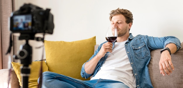 Beau blogueur s'enregistrant avec un verre de vin
