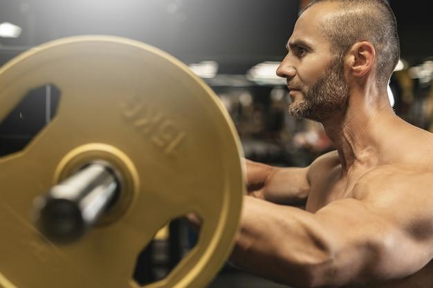 Beau bodybuilder barbu pendant son entraînement avec une barre dans la salle de gym