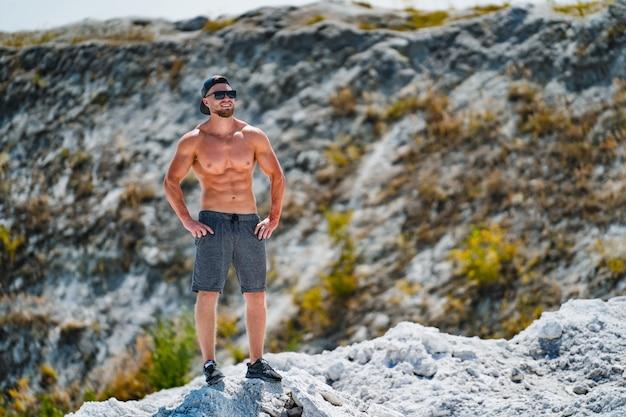 Beau bodybuilder avec un corps musclé parfait pose à l'extérieur. homme fort, torse nu, vêtu d'une casquette noire, regardant ailleurs.