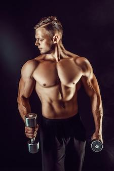 Beau bodybuilder, faire de l'exercice avec haltère