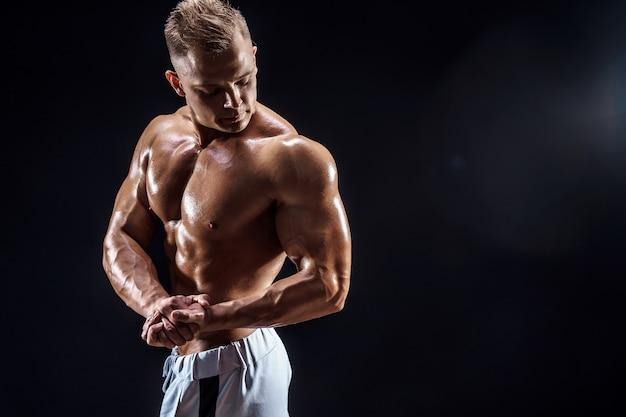 Beau bodybuilder fort posant dans