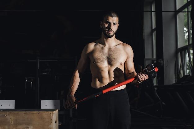 Beau bodybuilder avec les yeux fermés se repose après avoir fait des exercices de masse au gymnase vue de côté pleine longueur