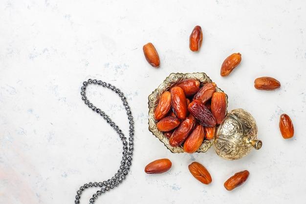 Beau bol plein de fruits de date symbolisant le ramadan, vue de dessus