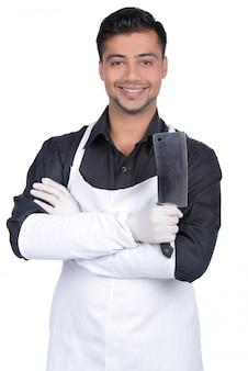 Beau boucher souriant et tenant un couteau.