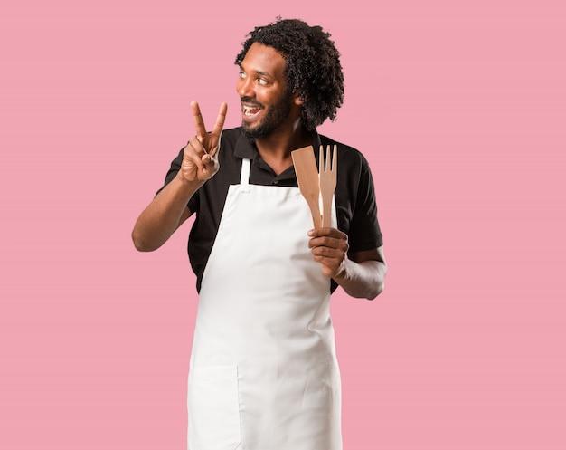 Beau boulanger afro-américain amusant et heureux, positif et naturel, fait un geste de victoire, concept de paix