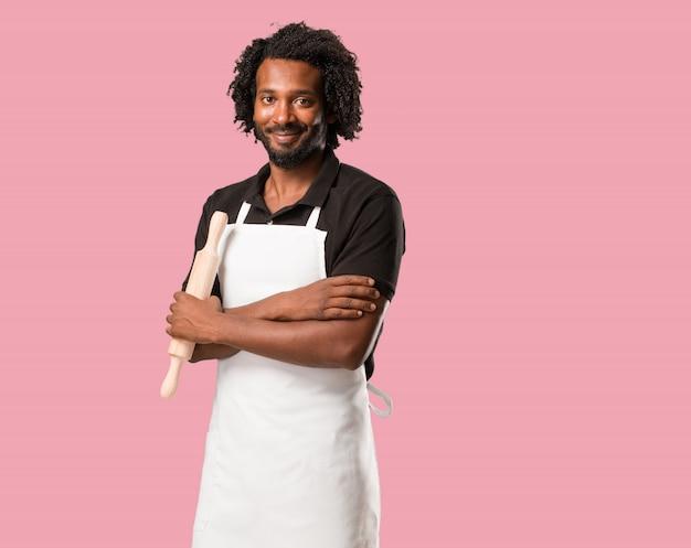 Beau boulanger afro-américain croisant ses bras, souriant et heureux, confiant et amical