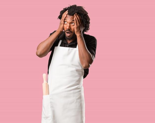 Beau boulanger afro-américain frustré et désespéré, en colère et triste avec les mains sur la tête