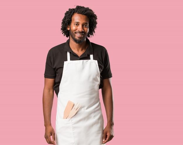 Beau boulanger afro-américain gai et avec un grand sourire, confiant, amical et sincère, exprimant la positivité et le succès