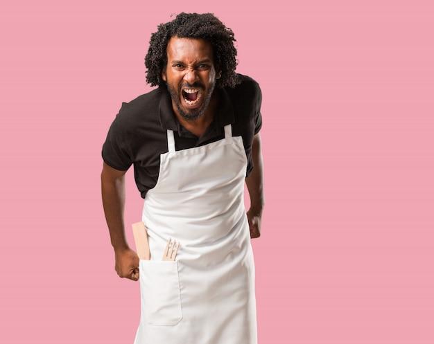 Beau boulanger afro-américain hurlant de colère, expression de folie et d'instabilité mentale