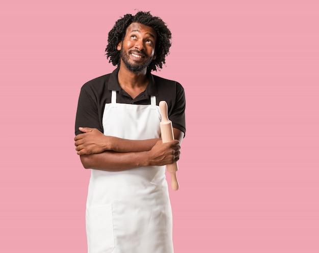 Beau boulanger afro-américain en levant, en pensant à quelque chose d'amusant et en ayant une idée