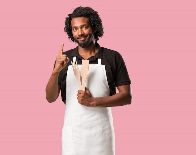 Beau boulanger afro-américain montrant le numéro un, symbole de comptage, concept de mathématiques, confiant et joyeux