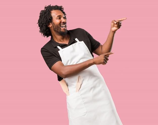 Beau boulanger afro-américain pointant sur le côté, souriant surpris présentant quelque chose