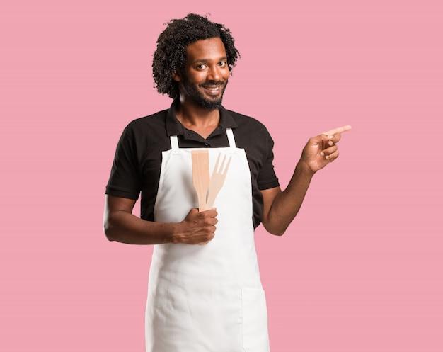 Beau boulanger afro-américain pointant sur le côté, souriant surpris de présenter quelque chose