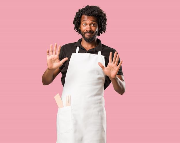 Beau boulanger afro-américain sérieux et déterminé, mettant la main devant, arrêtez gestur