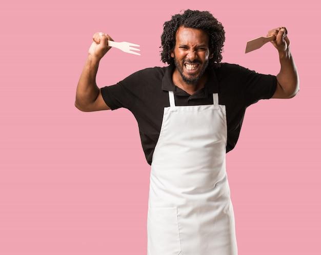 Beau boulanger afro-américain très en colère et contrarié, très tendu, hurlant furieux, négatif et fou