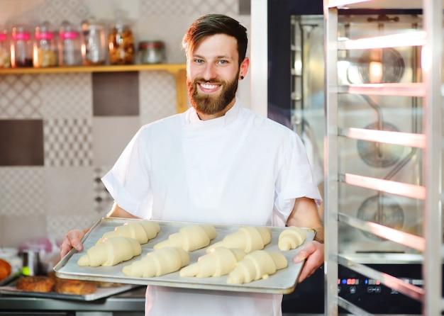 Un beau boulanger avec une barbe prépare des croissants pour la cuisson et sourit à la boulangerie