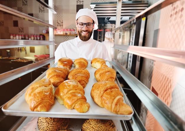 Beau boulanger mâle tient un plateau avec des croissants français devant une boulangerie et sourit.