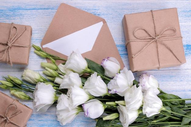 Beau bouquet blanc de fleurs eustoma avec des coffrets cadeaux et une enveloppe sur un fond en bois bleu