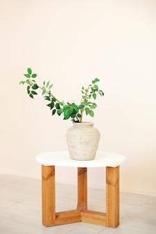 Beau bouquet de brindilles vertes avec des feuilles se dresse dans un vase sur une table en bois dans le salon. intérieur de la maison. scandinavie. rustique. composition florale. plante moderne dans un vase en céramique. mobilier écologique